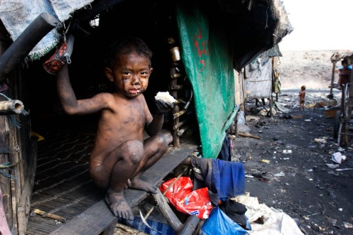A young boy peeks out of his small shack at Stung Meanchey Garbage Dump on Thursday, February 9, 2006 in Phnom Penh, Cambodia.  (Photo by Matthew Williams/ZUMA Press)